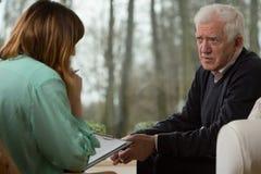 Psychiatrist and her elder patient. Image of young psychiatrist and her elder patient Stock Images