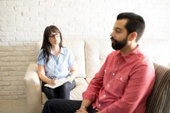 Psychiatrist listening to problems of male patient. Female psychiatrist listening the problems of young depressed male patient during the psychotherapy Royalty Free Stock Photo