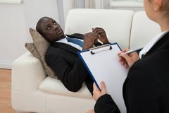 Psychiatrist Making Notes In Front Of Patient Stock Image