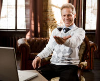 Psychiatrist man in office. Portrait of handsome psychiatrist man smiling and looking at camera. Psychiatrist man holding and representing hourglass in hand Royalty Free Stock Photo