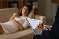 Psychiatrist session. Mature psychiatrist making notes during the session with female client Stock Photos