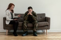 Psychiatrist talking to her angry patient while sitting on a sofa stock photos