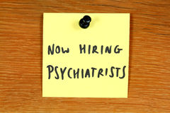 Psychiatry career. Sticky note with employment opportunity message - hiring psychiatrists. Psychiatry healthcare career. Bulletin board Stock Photography