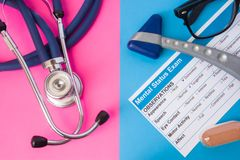 Psychiatry mental status exam, hourglass, reflex hummer and medical stethoscope in two colors background: blue and pink. Concept o Royalty Free Stock Photography