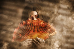 Psychic clairvoyant holding mystery and magic fan. Mystic fire woman holding a burning oriental fan in a smokey haze of mystery and magic. psychic Clairvoyant Stock Image