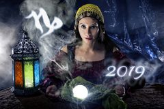 2019 Capricorn Predictions. Psychic or fortune teller with crystal ball and horoscope zodiac sign of capricorn royalty free stock photos