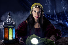 Psychic Fortune Teller. Female fortune teller doing a psychic reading with a cystal ball predicting fate or destiny and the future. The image depicts religion or royalty free stock photo