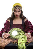 Psychic or Fortune Teller on White Background. Female fortune teller or psychic is concerned or depressed about a vision of the future seen in her crystal ball Stock Photo
