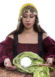 Psychic or Fortune Teller on White Background. Female psychic or fortune teller with a crystal ball on a white background Royalty Free Stock Photo