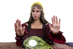 Psychic or Fortune Teller on White Background. Female psychic or fortune teller with her hands up telling viewer to stop or rejecting.  She is isolated on a Royalty Free Stock Image