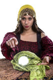 Psychic or Fortune Teller on White Background. Female psychic or fortune teller pointing finger forward at the viewer.  She has a crystal ball and isolated on a Stock Photo