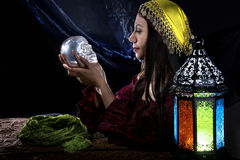 Psychic or Gypsy Halloween Costume. Female psychic or fortune teller holding a crystal skull trying to communicate with the dead Stock Photo