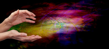 Psychic healing energy field. Female outstretched healing hands on psychedelic multi colored flowing energy formation background Royalty Free Stock Image