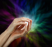 Psychic Protection. A pair of female hands with finger tips touching shaped into a gentle open cage and a multicolored radiating energy formation against a black Stock Photos