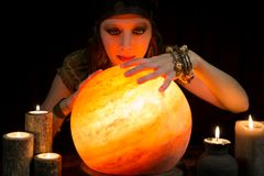 Psychic with a shining crystal ball. Young pretty Psychic with a shining crystal ball Royalty Free Stock Photo