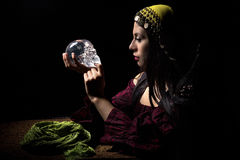 Psychic or a Spirit Medium. Female psychic or fortune teller holding a crystal skull trying to communicate with the dead Royalty Free Stock Photography