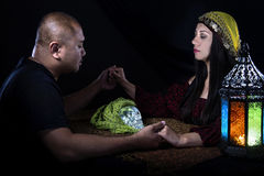 Psychic or a Spirit Medium. Psychic or fortune teller gypsy with a client doing a seance telepathic ritual Royalty Free Stock Photos