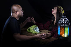 Psychic or a Spirit Medium. Psychic or fortune teller gypsy with a client doing a seance telepathic ritual Royalty Free Stock Image