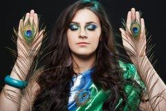 精神能力psychics与精神联络 拿着孔雀的女孩秀丽画象用羽毛装饰,明亮的衣裳 库存照片