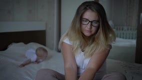 Psychische Gesundheit, gesorgte umgekippte Frau in den Brillen sitzt auf Bett auf Hintergrund des kriechenden Babys zu Hause stock video