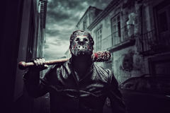 Psycho man in hockey mask with bloody baseball bat. Angry psycho man in hockey mask and black leather coat with bloody baseball bat with a chain wrapped around Stock Images