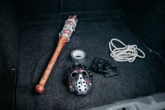 Psycho man instruments in opened car trunk, maniac. Hockey mask, baseball bat wrapped with bloody metal chain, leather fingerless gloves, duct tape and rope Stock Photography