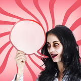 Psychodelic zombie with halloween communication. Psychodelic female zombie shouting out a halloween announcement through a blood red speech bubble Stock Photos