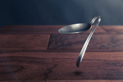 Psychokinesis concept with bent spoon. Spoon bending, psychokinesis, power of the mind Royalty Free Stock Images