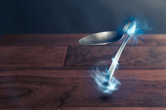 Psychokinesis concept with bent spoon. Spoon bending, psychokinesis, power of the mind Stock Photography