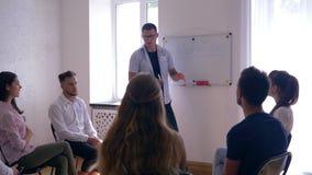 Psycholog prowadzi szkolenie dla młodzi ludzie podczas psychologicznego spotkania na tle deska z słowem - zbiory wideo