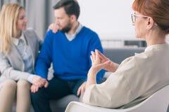 Psychologe, der glückliches verheiratetes Paar betrachtet stockbild