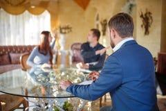Am Psychologen Young, welches die Paare, die an einem Glastisch sitzen, streiten, behandeln Sie das Sitzen in einem Stuhlhören lizenzfreie stockbilder