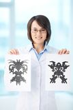 Psychological test. Vertical portrait of a charming psychologist showing two pictures of Rorschach test Stock Photo