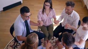 Psychologiczna rehabilitacja, grupy ludzi obsiadanie w okręgu i mienie ręki podczas terapii spotkania, zbiory