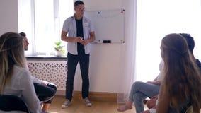 Psychologiczny szkolenie, mężczyzna psychologa wiodąca grupa ludzi mówi i pisze na blackboard słowie - motywacje zbiory wideo