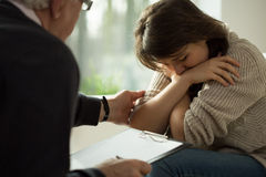 Psychologist comforting his patient. Close-up of psychologist comforting his depressed patient Royalty Free Stock Image
