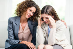 Psychologist counselling depressed woman at home. Psychologist counselling depressed women while sitting on sofa at home Stock Photos