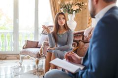 At the psychologist. A girl sitting on the couch tells the doctor her problems. At the psychologist. A girl in a gray dress sitting on the couch tells the Royalty Free Stock Image