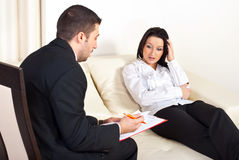 Psychologist giving prescription to woman. Psychologist giving prescription to a depressive woman in his office Stock Images