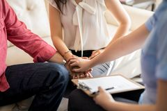 Psychologist supporting young couple. Psychologist holding hands of couple during a therapy session. Marriage counselor supporting young couple stock photography