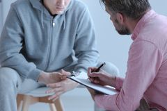 Psychologist interviewing his depressed patient during therapy royalty free stock photography