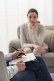 Psychologist listening to her patient. And writing down notes, mental health and counseling concept Stock Images