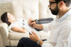 Psychologist making notes during a psychotherapy session. With female patient Royalty Free Stock Photo