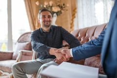 At the psychologist. A man sitting on the couch greeting a doctor Stock Image