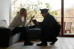 Psychologist of the police talking to victims after burglary. Psychologist of the police talking to a victim after a burglary with theft stock photo