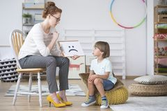 Psychologist showing picture to boy Stock Images