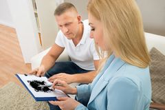 Psychologist Showing Rorschach Inkblot To Patient. Patient Looking At Rorschach Inkblot Held By Female Psychologist Stock Image