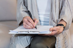 Psychologist sitting on the couch and taking notes Royalty Free Stock Photos