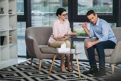 Psychologist talking with businessman. Female psychologist talking with upset businessman holding digital tablet in the office Royalty Free Stock Photo