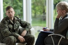Psychologist talking with despair soldier Stock Photos